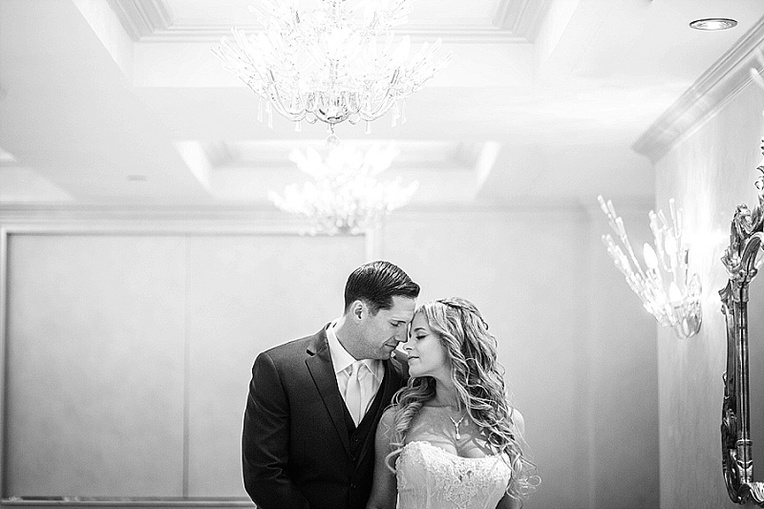 bride and groom embrace under a chandelier at The Grove NJ