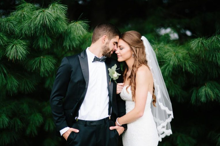 bride and groom share romantic kiss in front of pine tress at rose bank winery photographed by allie skylar photography